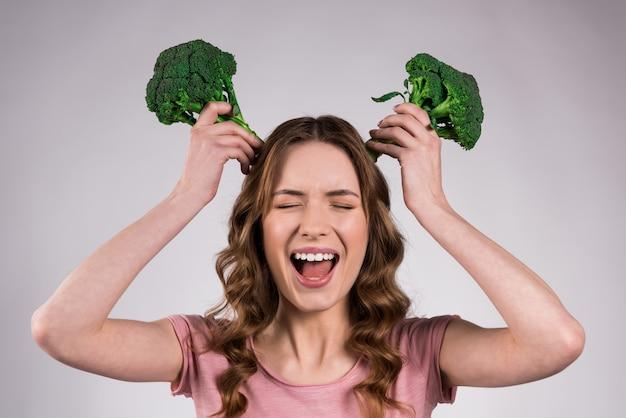 Dziewczyna krzyczy i kładzie brokuły na głowie.