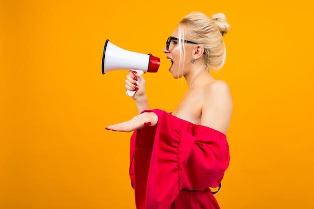 Dziewczyna krzyczy wiadomości w głośniku i stoi bokiem na żółtej ścianie