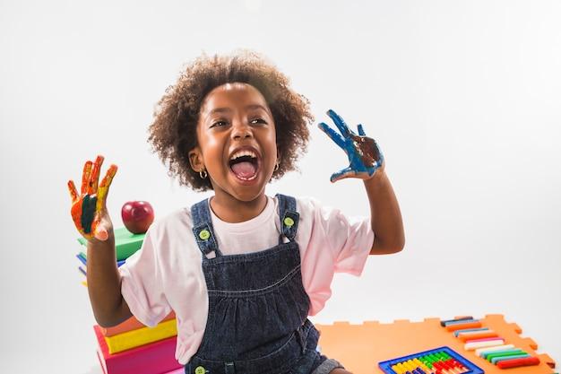 Dziewczyna krzyczy z rękami w farbie w studiu