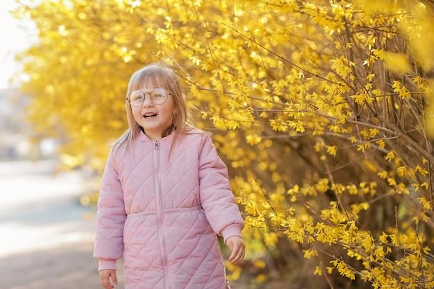 Dziewczyna krzywi się na spacerze jesienią. dziecko w różowym płaszczu na ulicy gryzmoli i zakrywa uszy dłońmi