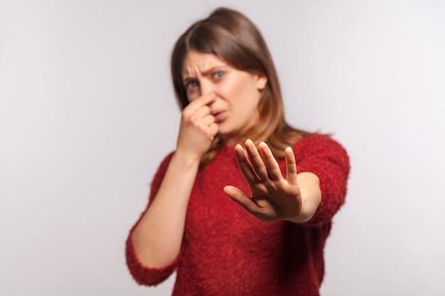 Dziewczyna krzywiąc się z obrzydzeniem i szczypiąc się w nos pokazując stop