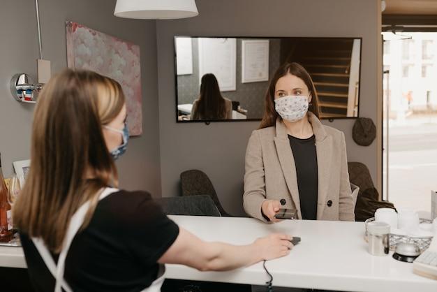 Dziewczyna, która nosi medyczną maskę na twarz, korzysta z telefonu komórkowego, aby płacić zbliżeniową technologią pay pass. barista w masce na twarz podaje klientowi terminal nfc za zapłatę.