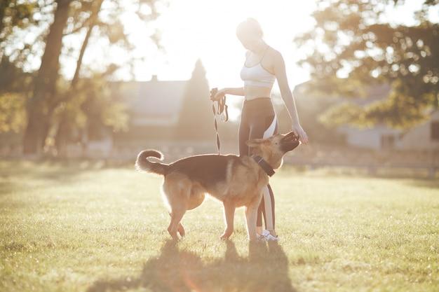 Dziewczyna, która wyprowadza swojego psa na wschód słońca