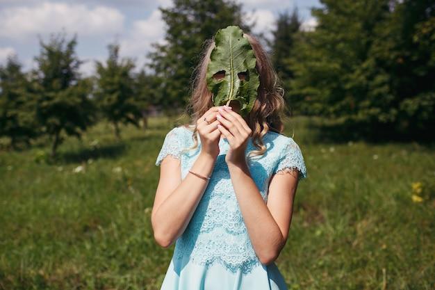 Dziewczyna, której twarz ukryta jest za wielkim liściem łopianu