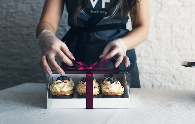 Dziewczyna kucharka w szarym fartuchu pakuje babeczki ze śmietaną w ozdobne pudełko, by wysłać zamówienie do klienta. pieczenie w domu.