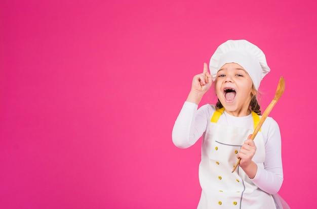 Dziewczyna kucharz z kopyścią pokazuje palec wskazującego