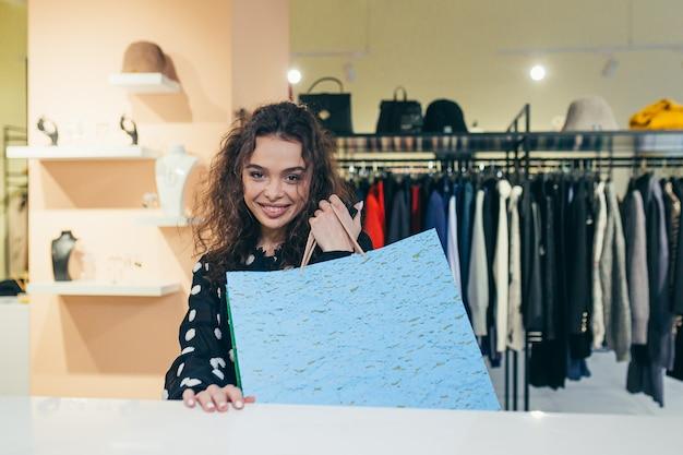 Dziewczyna kupująca płaci przy kasie za dobre ubrania w sklepie kartą kredytową
