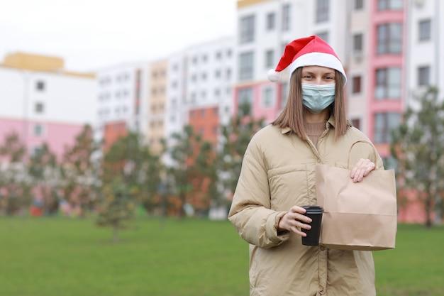 Dziewczyna kurierka w ochronnej masce i czapce mikołaja trzyma papierową torbę z produktami i filiżankę kawy