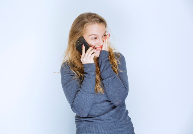 Dziewczyna ładnie rozmawia przez telefon ze swoim partnerem.