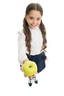 Dziewczyna ładny uczeń trzyma jabłko owoc białe tło. dziecięca dziewczyna mundurek szkolny oferuje jabłko. dziecko inteligentne dziecko uśmiechniętą twarz wybrać zdrową przekąskę. koncepcja przekąski na lunch w szkole. zdrowe odżywianie.