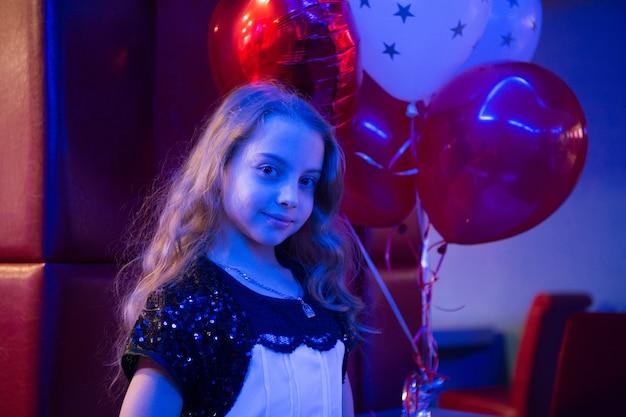 Dziewczyna ładny uśmiechający się dziecko trzymać kilka balonów oświetlonych niebieskim światłem. dziewczyna z balonami świętować urodziny w kręgielni. urodziny w kręgle. pomysły, jak świętować urodziny dla nastolatków.