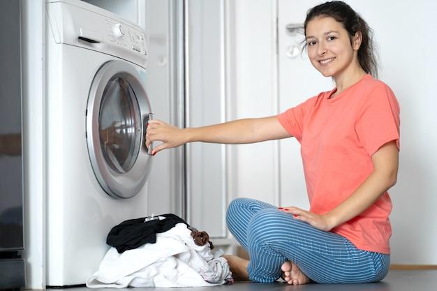 Dziewczyna ładuje brudne pranie do pralki, siedząc na podłodze w mieszkaniu. dzień prania, prace domowe