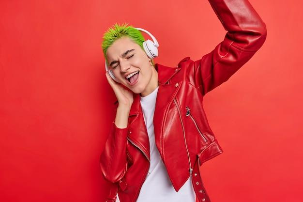 Dziewczyna łapie każdy kawałek muzyki słucha ulubionej piosenki w bezprzewodowych słuchawkach ma na sobie skórzaną kurtkę porusza się na czerwono