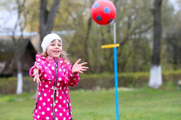 Dziewczyna łapie piłkę. gry dla dzieci na ulicy