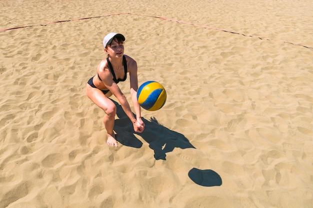 Dziewczyna łapie piłkę na piasku, grając w siatkówkę plażową. gry sportowe na świeżym powietrzu. koncepcja zdrowego stylu życia.
