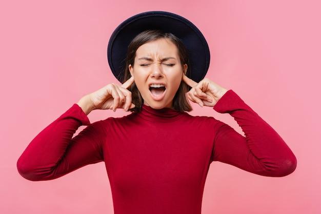Dziewczyna laufhing zakryła uszy palcami. ludzie, koncepcja języka ciała.
