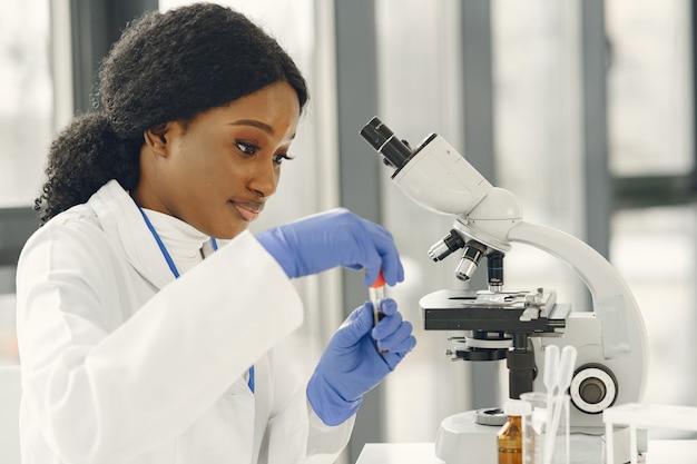Dziewczyna lekarz medycyny pracy z mikroskopem. młoda kobieta naukowiec robi badania nad szczepionkami.