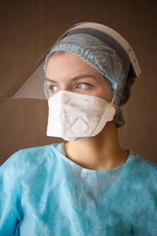 Dziewczyna lekarz pielęgniarka w kombinezonie ochronnym i masce i okularach ochronnych
