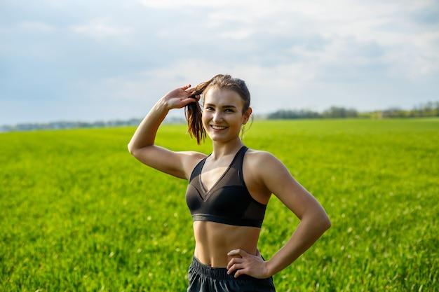 Dziewczyna lekkoatletka robi rozgrzewkę na świeżym powietrzu, ćwiczenia na mięśnie. młoda kobieta uprawia sport, zdrowy styl życia, atletyczną sylwetkę. jest w stroju sportowym, czarnym topie i szortach. koncepcja sportu.