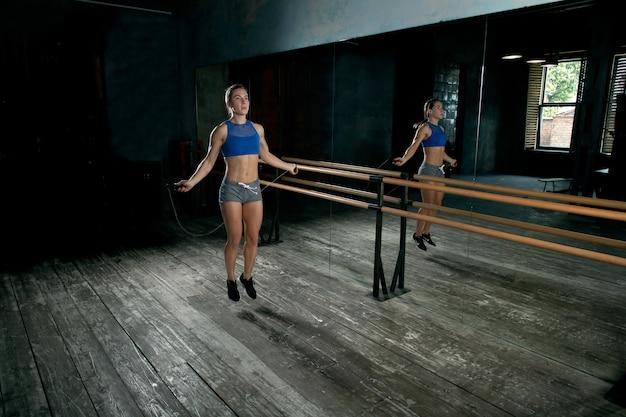 Dziewczyna lekkoatletka skakanka na skakance przed lustrem w sali gimnastycznej