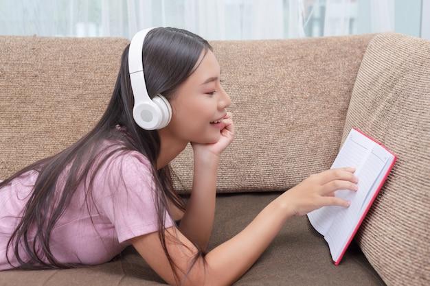 Dziewczyna leżąc na kanapie, słuchanie muzyki i czytanie książek.