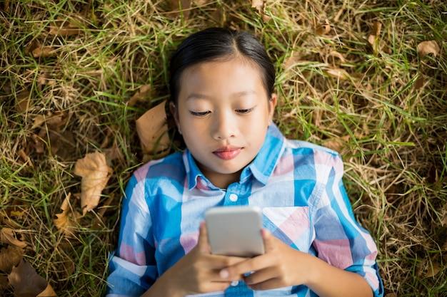 Dziewczyna leżąc na trawie i przy użyciu telefonu komórkowego