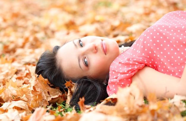 Dziewczyna leżąca na jesiennych liściach klonu