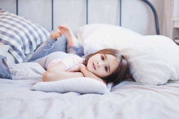 Dziewczyna leżąca na łóżku, mała dziewczynka odpoczywająca wśród poduszek i koców, marzenia