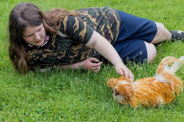 Dziewczyna leżąca na trawie z kurczakiem ładny padovana.