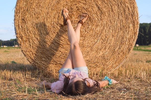 Dziewczyna leżąca na ziemi opierając nogi na dużej beli słomy