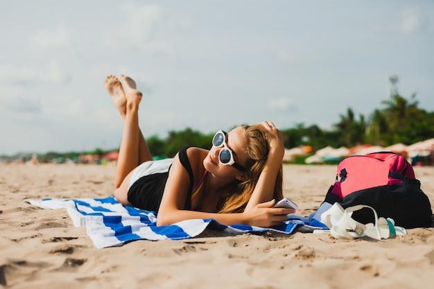 Dziewczyna leżącego twarzą w dół z okulary patrząc na telefon komórkowy