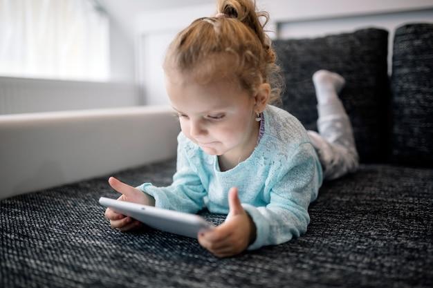 Dziewczyna leży na kanapie i gra w tabletkę
