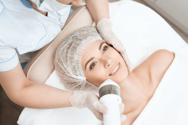 Dziewczyna leży na kanapie w nowoczesnym salonie kosmetologii.