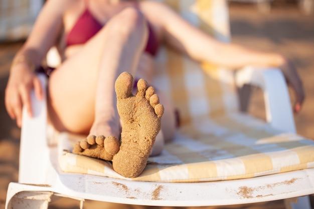 Dziewczyna leży na leżaku. stopa w piasku