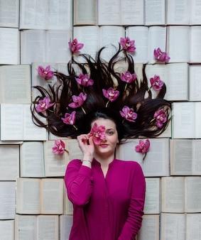 Dziewczyna leży na otwartych książkach, ubrana w fuksyjną bluzkę z kwiatami magnolii we włosach