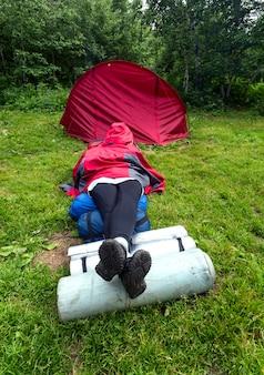 Dziewczyna leży na trawie w pobliżu namiotu w lesie