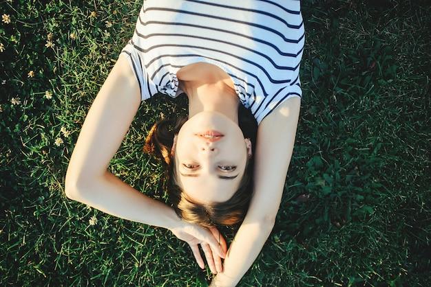 Dziewczyna leży na trawie w słońcu, widok z góry
