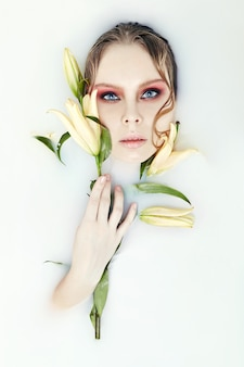 Dziewczyna leży w kąpieli z mlekiem i lily w dłoniach