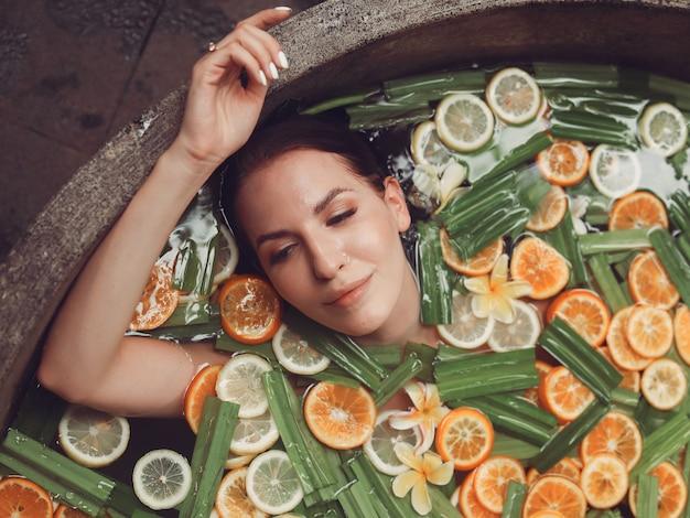 Dziewczyna leży w okrągłej wannie z owocami
