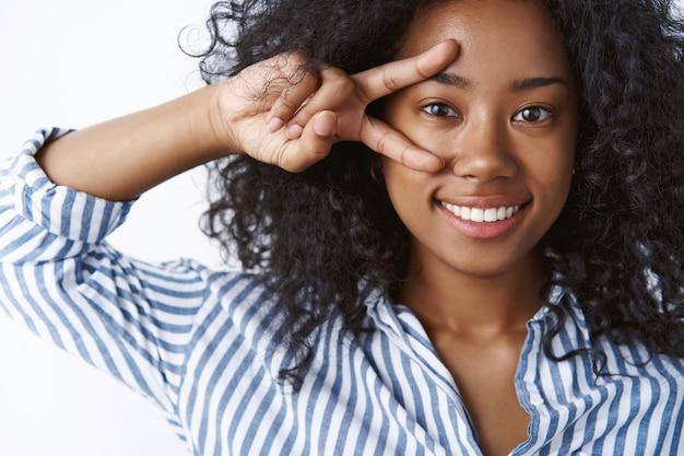 Dziewczyna lubi anime pokazujące znak pokoju. portret wzruszający beztroski szczęśliwa ciemnoskóra młoda kobieta kręcone fryzury sprawiają, że dyskotekowy gest zwycięstwa w pobliżu oka uczucie niesamowitej radości, stojąca biała ściana