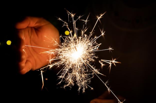 Dziewczyna lubi bawić się małym fajerwerkiem w ręku, świętując w boże narodzenie i nowy rok.