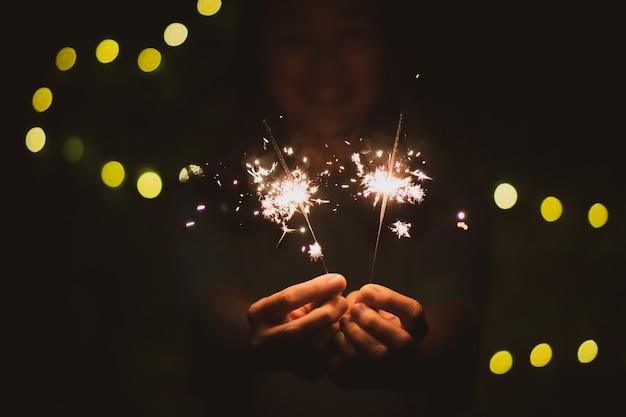 Dziewczyna lubi bawić się małym fajerwerkiem w ręku