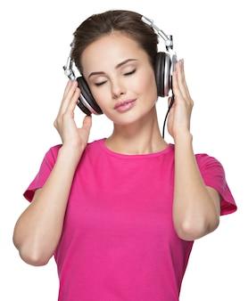 Dziewczyna lubi słuchać muzyki na słuchawkach na białym tle