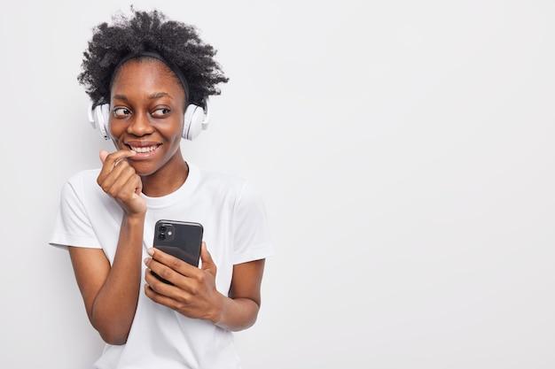 Dziewczyna ma aplikację muzyczną słucha świetnej piosenki online nosi luźną koszulkę komunikuje się online zamierza mieć zdalną lekcję internetową pozuje na białym