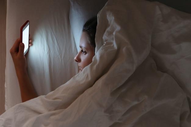 Dziewczyna ma bezsenność z powodu używania smartfona w nocy.