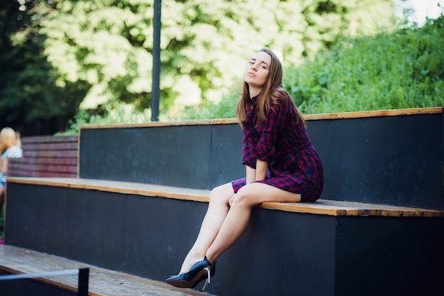 Dziewczyna ma na sobie sukienkę w kratkę, siedząc w skateparku