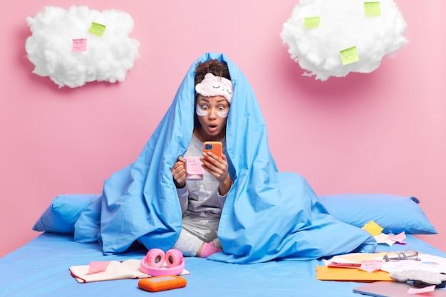Dziewczyna ma przerwę na kawę wpatruje się w smartfona wyświetlacz czyta szokujące wiadomości na portalach społecznościowych owinięta ciepłym kocem cieszy się domową atmosferą siedzi ze skrzyżowanymi nogami na łóżku studiuje z daleka