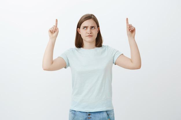 Dziewczyna ma wątpliwości, czy produkt jest kiepski. intensywnie niezadowolona urocza dziewczyna z wielkim marszczonym uchem, patrząca i wskazująca w górę z niechęcią i wątpliwościami, wahająca się, czy wybór jest właściwy pozując na białej ścianie