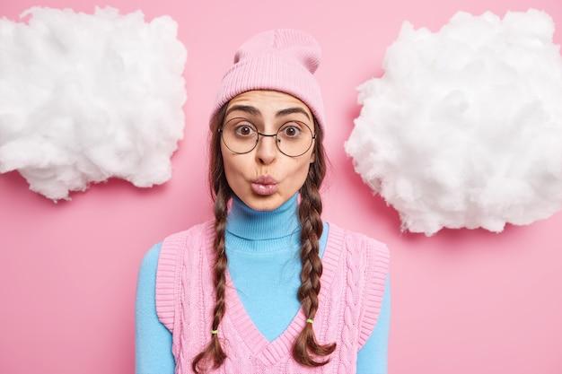 Dziewczyna ma zaokrąglone usta chce cię pocałować ma dwa uczesane warkocze nosi stylowe okulary na różowo