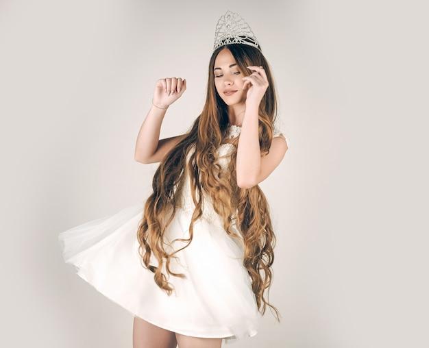 Dziewczyna ma zdrowe, długie włosy. fryzjer i kosmetyki. salon piękności i moda ślubna. pielęgnacja włosów i królowa balu. kobieta z długimi włosami białą sukienkę i koronę.